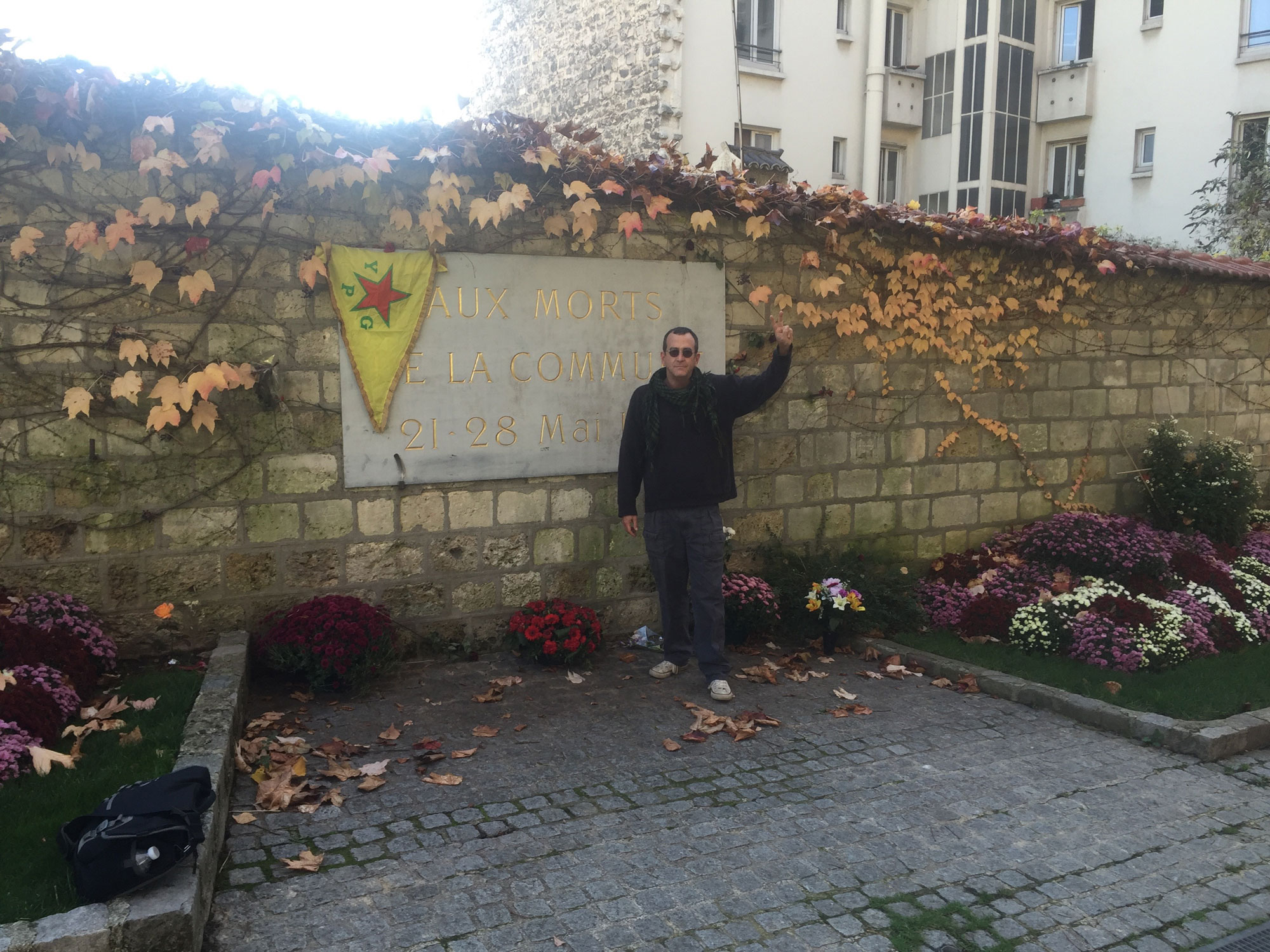 Paul Z. Simons at the Cimetière du Père Lachaise in Paris where the last participants in the Paris Commune were executed, displaying a YPG flag.