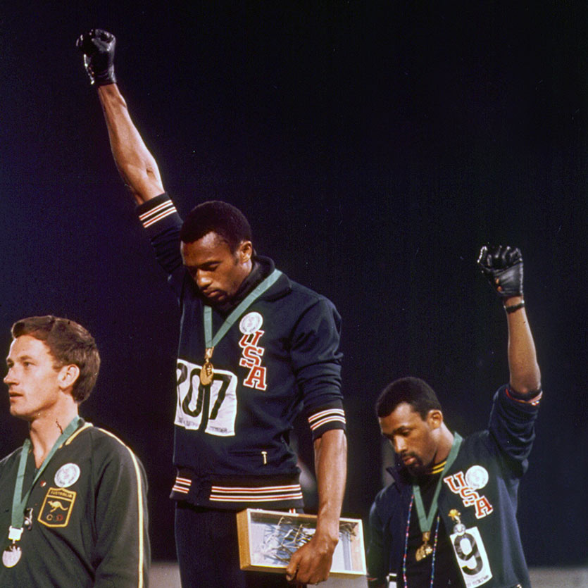 1968 Olympics Black Power salute raised by the African-American athletes Tommie Smith and John Carlos during their medal ceremony at the 1968 Summer Olympics in the Olympic Stadium in Mexico City. As they turned to face their flags and hear the American national anthem, they each raised a black-gloved fist and kept them raised until the anthem had finished