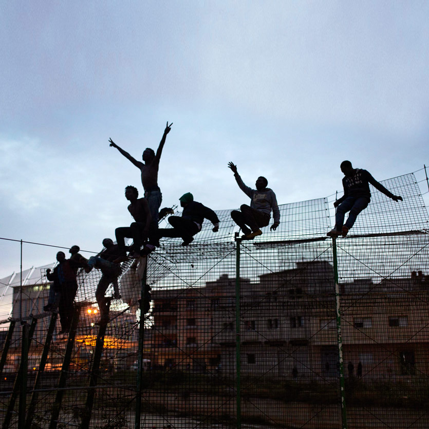 a grouple of people sits upon a tall boundary fence they have climbed