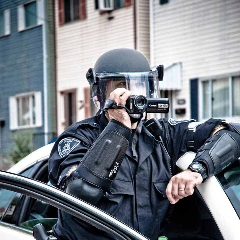 a cop dressed in fancy riot gear leans out of his open patrol car door and uses a camcorder to record protestors who are not pictured