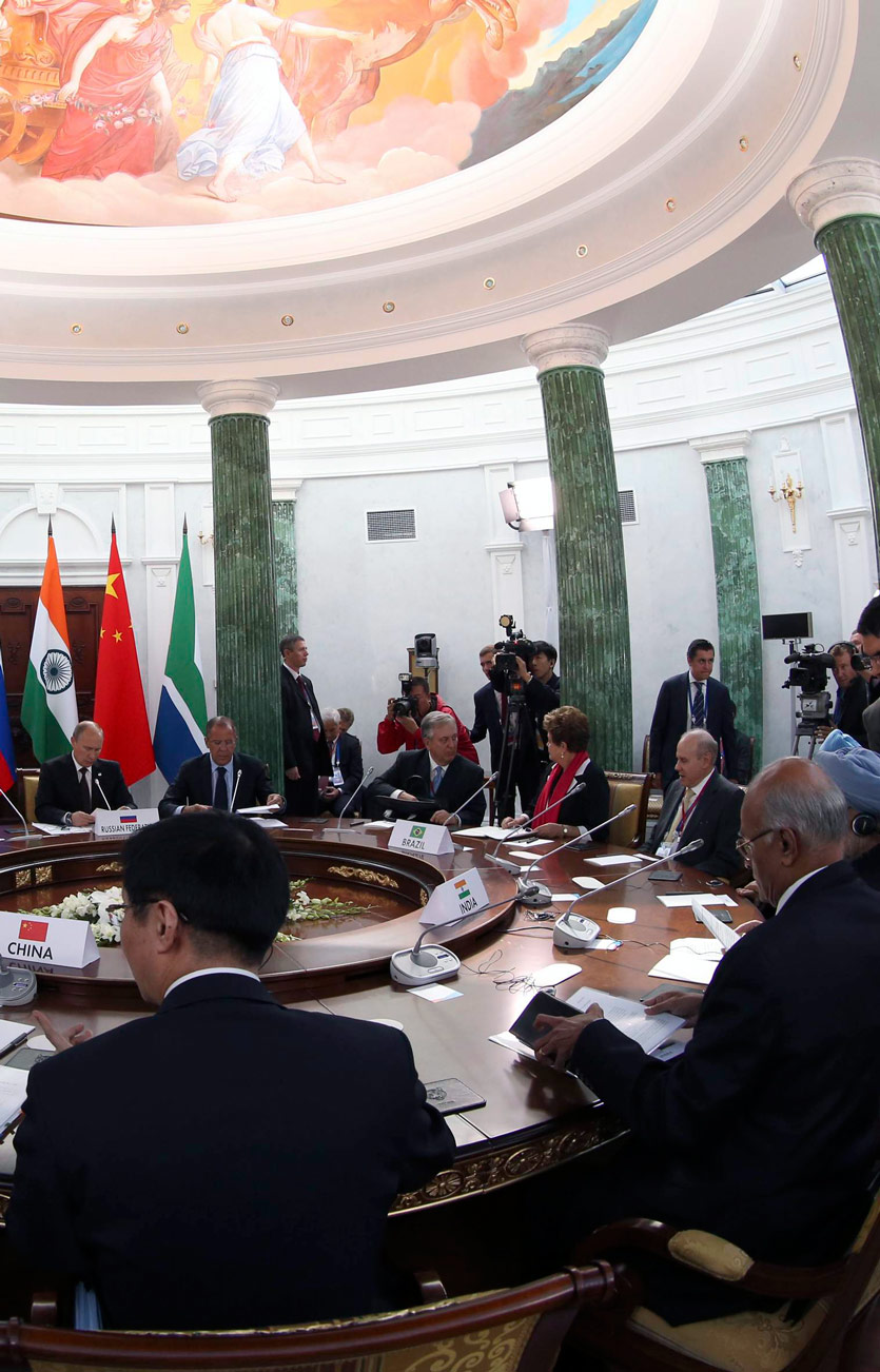 large conference table at which world leaders are seated, surrounded by press and their minions, a summitt meeting with greek columns of marble and a traditional fresco in the dome above