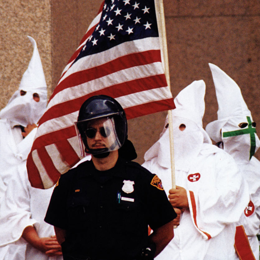a mustachioed cop in riot gear wearing aviator sunglasses stands guard in fron of severl Ku Klux Klan members in full robes, one of whom carries a American flag
