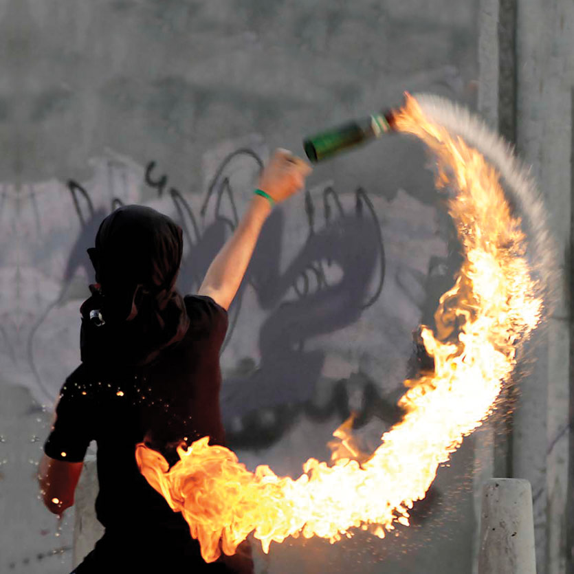 a protestor with his face concealed in the act of throwing a lit molotov cocktail during a protest, in front of a huge concrete wall