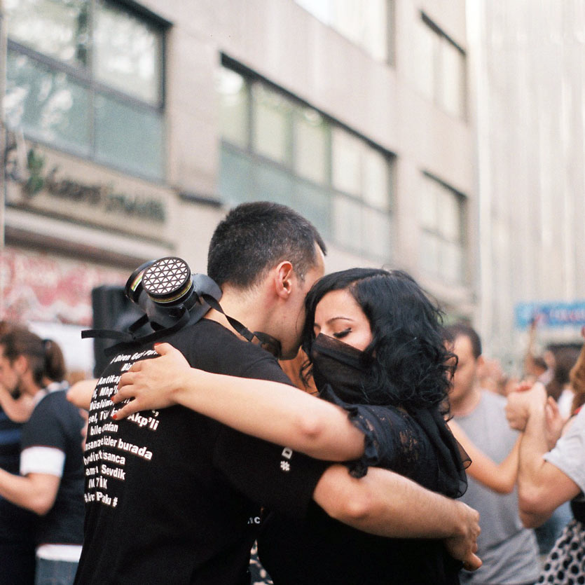 two protestors, adorned with gas masks and balaclavas, dance the tango together in the street