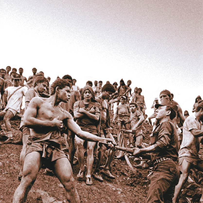 a worker in a gold mine confronts soldier keeping guard and grabs his rifle by the barrel as a crowd of workers watch