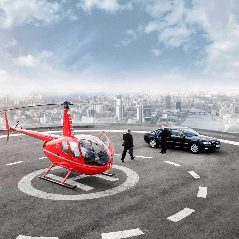 a chauffeur holds open the door to a large Audi as a wealthy businessman exits a helicopter and proceeds across the helipad towards the car