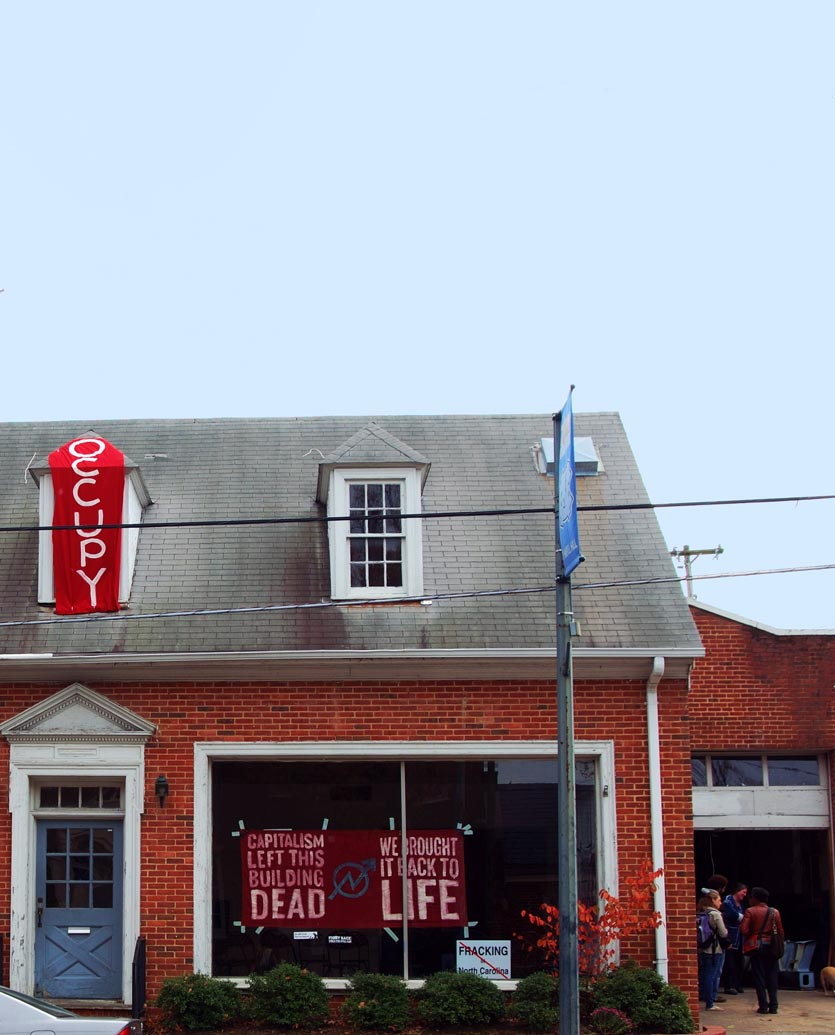 an abandoned building, now occupied, with protest banners in the window, being used as community organizing location