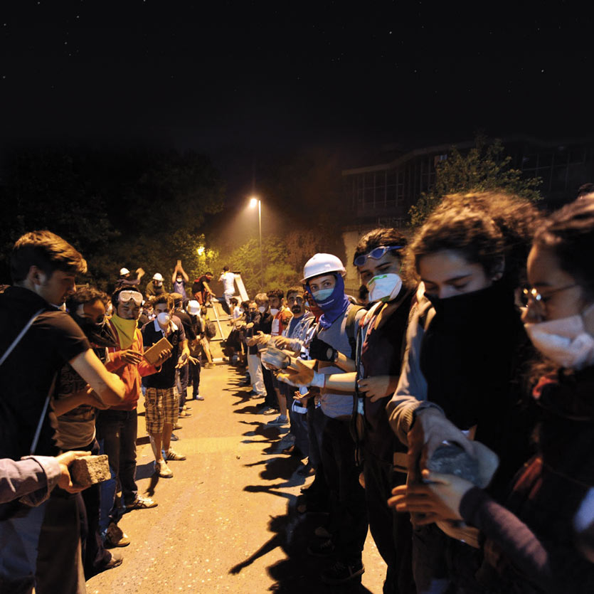 at night, lit by streetlights, young protestors in Turkey form a fire-brigade-line to transport cobblestones to the front lines of a conforntation with police