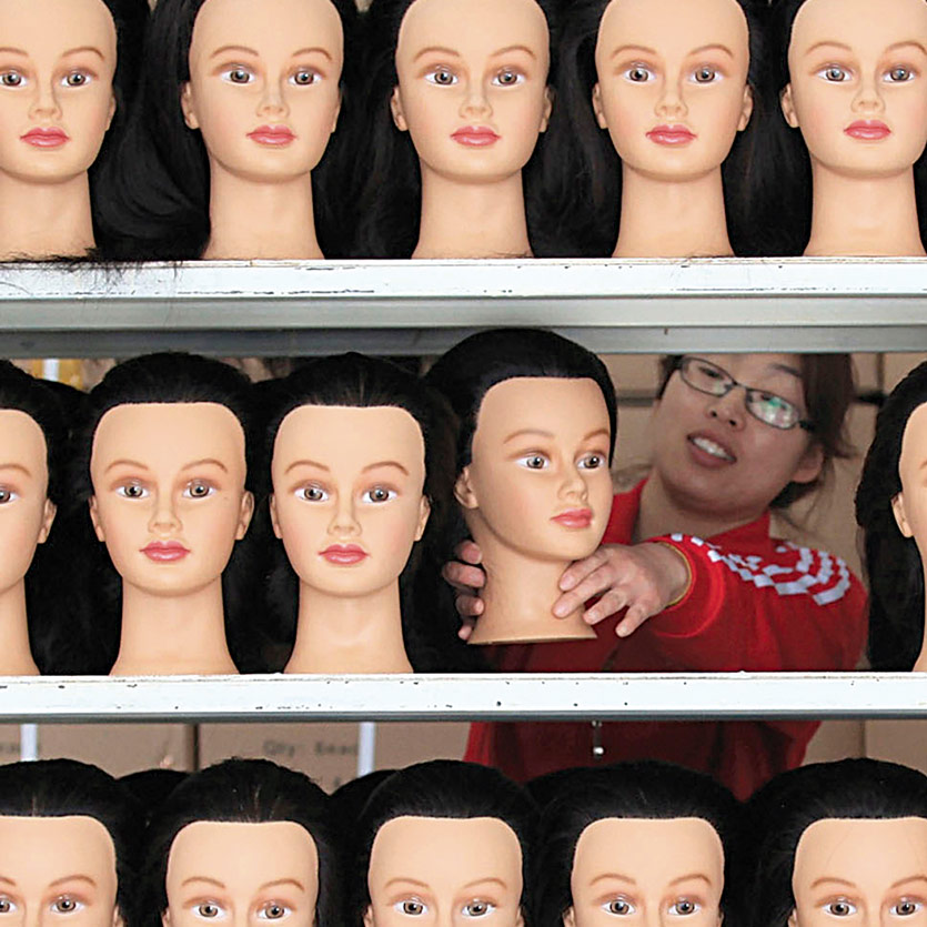 a woman of asian ethnicity works as a mannequin factory stocking a shelves that are full of caucasian mannequin heads
