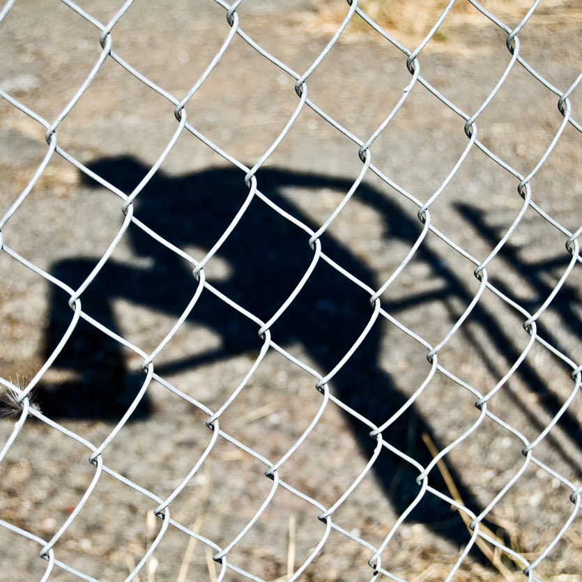 shadow of a person climbing over a barbed-wire fence